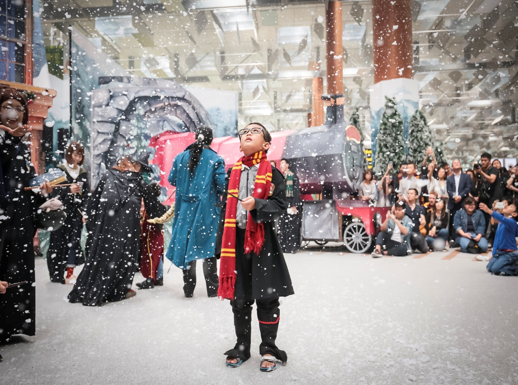 A young fan entralled by the snow at a wintry Hogsmeade